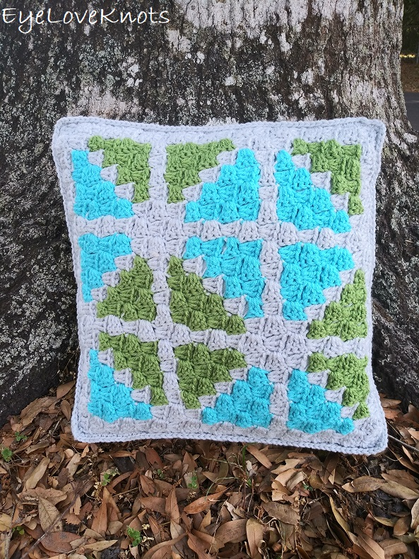 Finished C2C Window Pane Throw Pillow next to a tree