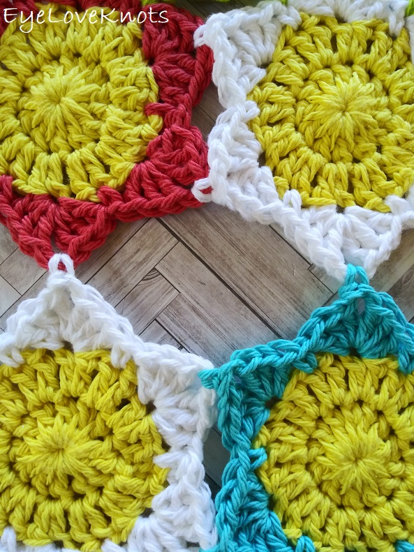 four crocheted flowers attached together with empty space in between EyeLoveKnots