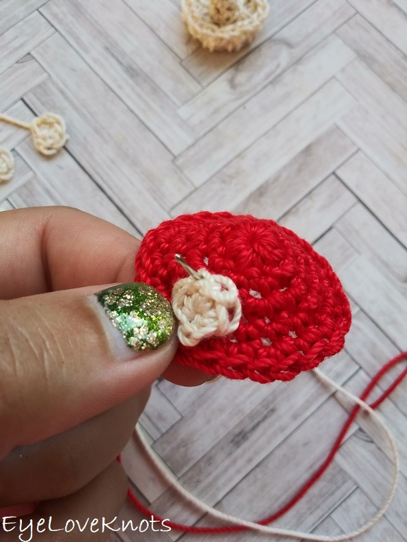 needle coming from the bottom up through the back loop of the crocheted dot