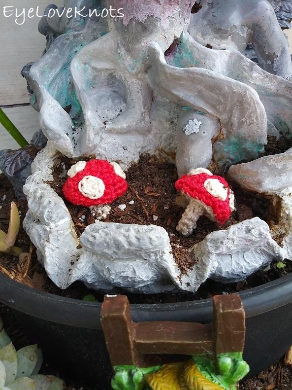 crocheted toadstools displayed in fairy garden