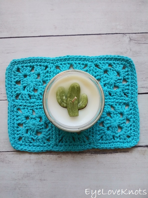 Finished blue granny square doily with candle on top.