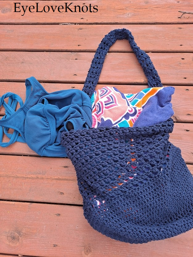 Crocheted bucket bag beauty laid flat on deck filled with beach items.