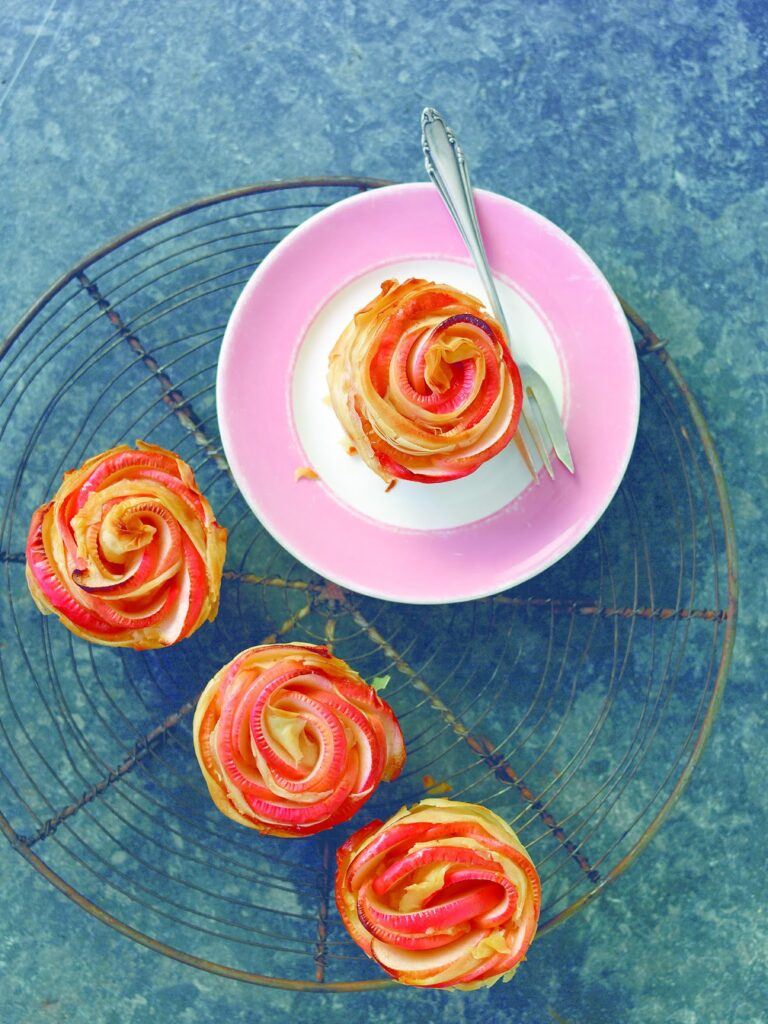 four cinnamon rose cupcakes on a cake plate