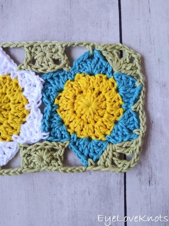 close up of blue crocheted flower of floral mug rug EyeLoveKnots